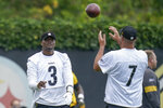Pittsburgh Steelers quarterback Dwayne Haskins (3) tosses a football to Ben Roethlisberger during an NFL football practice, Thursday, July 22, 2021, in Pittsburgh. (AP Photo/Keith Srakocic)