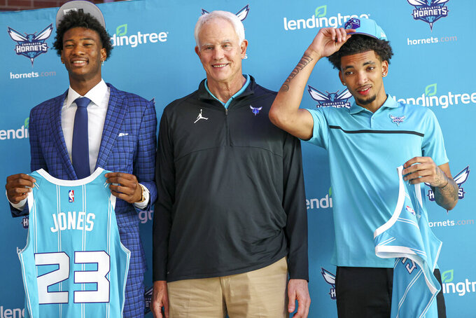 Charlotte Hornets general manager Mitch Kupchak, center, stands with 2021 NBA draft picks Kai Jones, left, and James Bouknight at a news conference in Charlotte, N.C., Friday, July 30, 2021. (AP Photo/Nell Redmond)