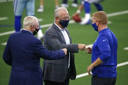 Dallas Cowboys team owner Jerry Jones, left, Stephen Jones, center, and New York Giants offensive coordinator Jason Garrett, right, greet each other before an NFL football game in Arlington, Texas, Sunday, Oct. 11, 2020. The game marks the first time Garrett has returned to play against the team he was the head coach of last season. (AP Photo/Michael Ainsworth)