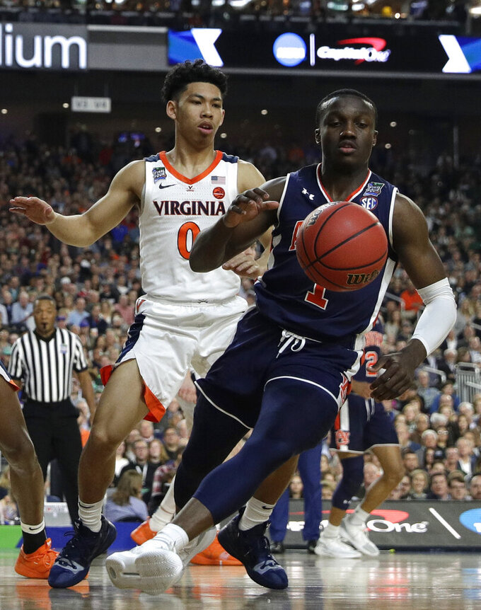 Auburn guard Jared Harper fights for a loose ball with Virginia guard Kihei Clark, left, during the first half in the semifinals of the Final Four NCAA college basketball tournament, Saturday, April 6, 2019, in Minneapolis. (AP Photo/David J. Phillip)