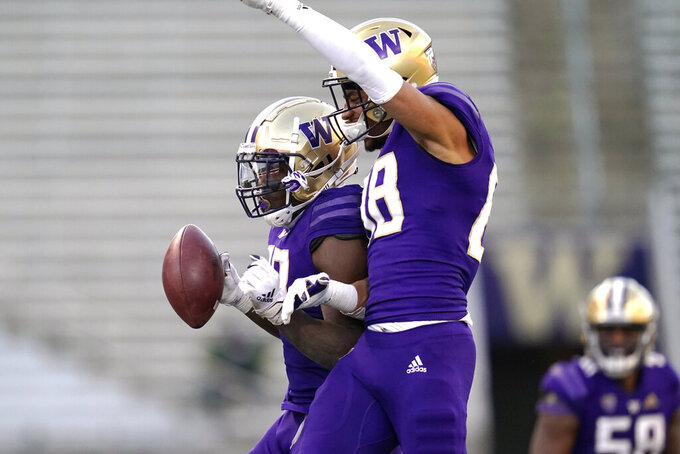 Washington's Edefuan Ulofoshio, left, celebrates his interception against Stanford with teammate Ty Jones during the second half of an NCAA college football game Saturday, Dec. 5, 2020, in Seattle. Stanford won 31-26. (AP Photo/Elaine Thompson)