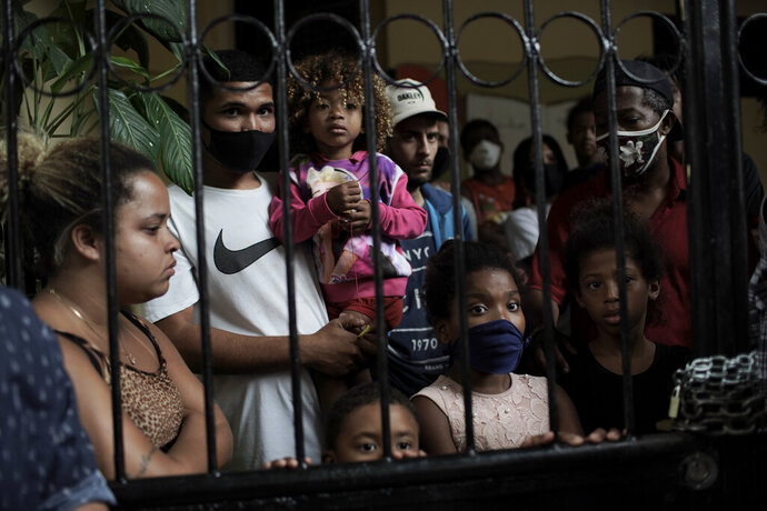 FILE - In this Sept. 15, 2020 file photo, squatters peer from behind the iron gate of a house that about 19 families have been occupying for close to a year, before being evicted, amid the new coronavirus pandemic in Rio de Janeiro, Brazil. Poor people in Brazil are struggling to cope with less pandemic aid from the government and jumping food prices, with millions expected to slip back into poverty. (AP Photo/Silvia Izquierdo, File)