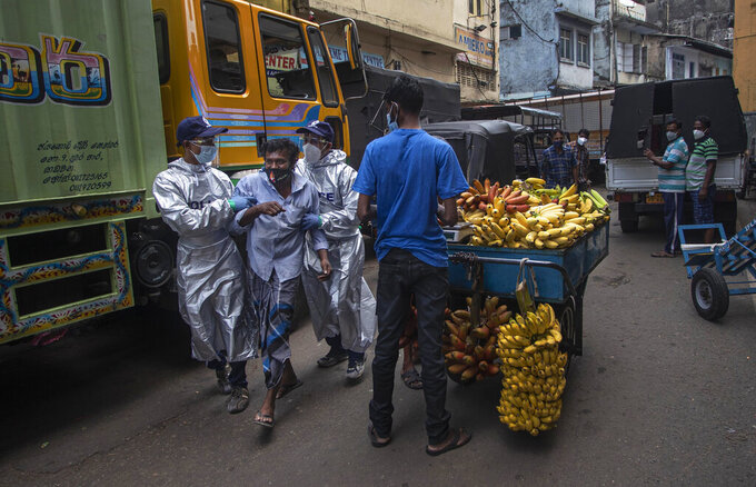 Sri Lankan police officials detain a man who violated the COVID-19 guidelines imposed by the authorities to curb the spread of the coronavirus in Colombo, Sri Lanka, Friday, May 7, 2021. (AP Photo/Eranga Jayawardena)