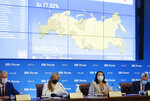 Head of Russian Central Election Commission Ella Pamfilova, center left, and Secretary of the Commission Maya Grishina, center right, wearing a face mask and gloves to protect against coronavirus attend a news conference in Moscow, Russia, Thursday, July 2, 2020, sits in front of the screen showing a map of Russia with signs that read: