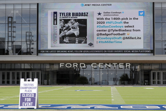 A sign sits on a artificial field frequented by fans at the Ford Center by The Star, the Dallas Cowboys headquarters and training facility, as a large video screen on the exterior wall of the building broadcast the team's latest selection in the NFL football draft in Frisco, Texas, Saturday April 25, 2020. (AP Photo/Tony Gutierrez)