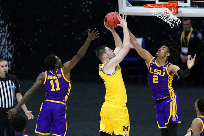 Michigan center Hunter Dickinson, center, drives to the basket between LSU defenders Josh LeBlanc Sr., left, and Trendon Watford (2) during the first half of a second-round game in the NCAA men's college basketball tournament at Lucas Oil Stadium Monday, March 22, 2021, in Indianapolis. (AP Photo/AJ Mast)