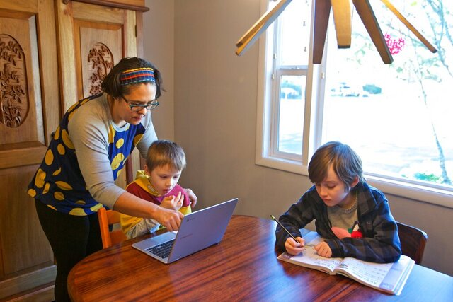 In this March 17, 2020 photo Olivia Bucks, left, helps her son Keith Bucks, center, with an online class assignment while Ashton Morris, right, works on a handwriting lesson from their first grade class at Arco Iris Spanish Immersion School in Beaverton, Ore. Bucks works from home selling books online and now spends her time between working on her business and helping her sons with their school work. They are using her work laptop to access their classroom assignments. (AP Photo/Craig Mitchelldyer)