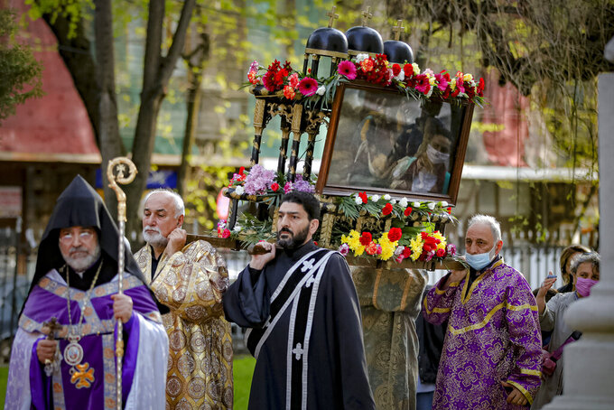 Members of the Armenian community in Romania, wearing face masks, are reflected in an icon as clergymen carry a structure symbolizing the tomb of Jesus Christ during a Good Friday religious service, at the Armenian Church in Bucharest, Romania, Friday, April 30, 2021. (AP Photo/Vadim Ghirda)