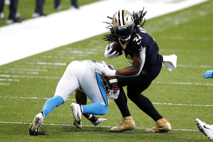 New Orleans Saints running back Alvin Kamara (41) carries against Carolina Panthers cornerback Troy Pride in the first half of an NFL football game in New Orleans, Sunday, Oct. 25, 2020. (AP Photo/Butch Dill)