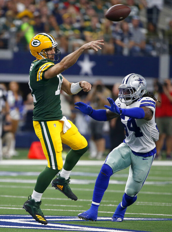 Green Bay Packers quarterback Aaron Rodgers, left, throws a pass as Dallas Cowboys middle linebacker Jaylon Smith (54) defends in the first half of an NFL football game in Arlington, Texas, Sunday, Oct. 6, 2019. (AP Photo/Ron Jenkins)