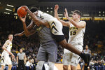 Northwestern center Dererk Pardon (5) is fouled by Iowa forward Tyler Cook while driving to the basket during the first half of an NCAA college basketball game, Sunday, Feb. 10, 2019, in Iowa City, Iowa. Iowa forward Luka Garza, right, looks on. (AP Photo/Charlie Neibergall)