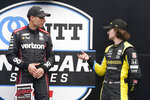 Will Power, left, of Australia, talks with Colton Herta on victory podium following and IndyCar auto race at Indianapolis Motor Speedway, Saturday, Aug. 14, 2021, in Indianapolis. Power won the race and Herta finished third. (AP Photo/Darron Cummings)