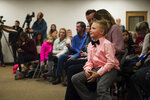 Range View Elementary School third grader Dane Best sits on the lap of his mother, Brooke Best, during a town board meeting where he presented his argument to change a law in Severance that bans snowball fights on Monday, Dec. 3, 2018, at the Town Hall in Severance, Colo. The 9-year-old boy later convinced the leaders of the small northern Colorado town to overturn a nearly century-old ban on snowball fights. (Timothy Hurst/The Coloradoan via AP)