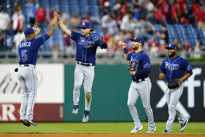 Tampa Bay Rays' Wander Franco, left, and Brett Phillips celebrate with teammates after the Rays won an interleague baseball game against the Philadelphia Phillies, Wednesday, Aug. 25, 2021, in Philadelphia. (AP Photo/Matt Slocum)