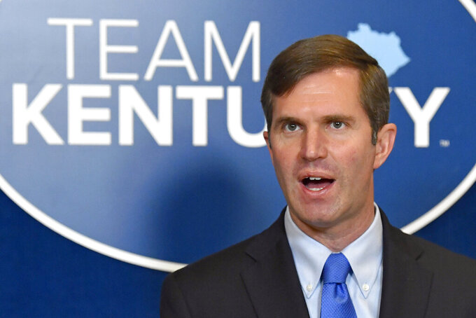 FILE - In this April 7, 2021, file photo, Kentucky Gov. Andy Beshear speaks to reporters at the Kentucky State Capitol in Frankfort, Ky.  The Kentucky governor's efforts to aggressively combat COVID-19 suffered a landmark legal defeat Saturday, Aug. 21,  as the state's high court cleared the way for new laws to rein in his emergency powers.  (AP Photo/Timothy D. Easley)