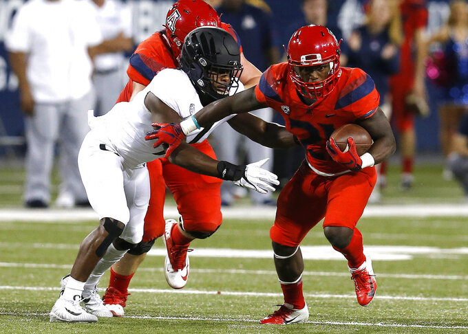 Arizona running back J.J. Taylor (21) stiff arms an Oregon defender in the first half during an NCAA college football game, Saturday, Oct. 27, 2018, in Tucson, Ariz. (AP Photo/Rick Scuteri)