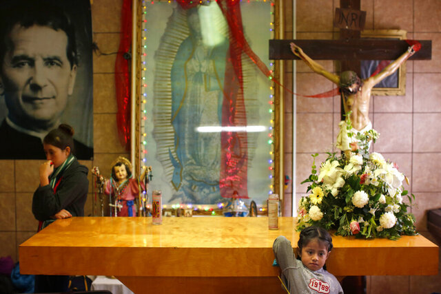 In this Feb. 26, 2019 photo, migrants rest in the chapel of the San Juan Bosco migrant shelter, in Nogales, Mexico. For years, Catholic-led, U-S.-based nonprofits have been at the forefront of efforts to support migrants and asylum seekers along the Mexican border. Tough new border policies, coupled with the COVID-19 pandemic, have drastically changed their work, much of which now takes place in Mexico. (AP Photo/Dario Lopez-Mills)