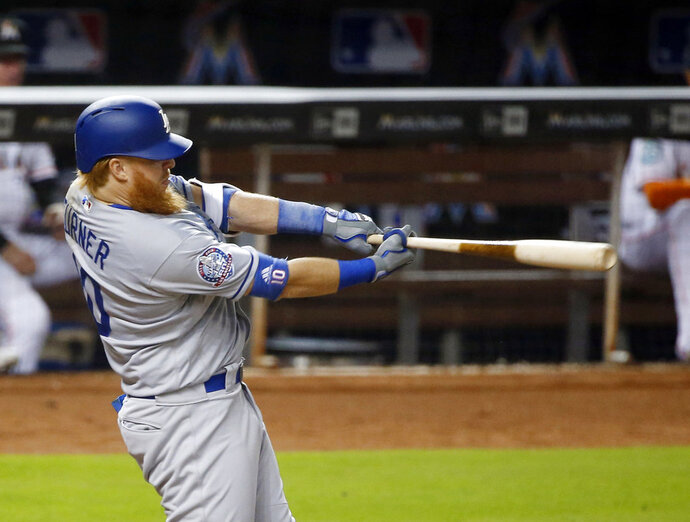 Los Angeles Dodgers' Justin Turner hits a double scoring Yasiel Puig, Austin Barnes and Chris Taylor during the third inning of a baseball game against the Miami Marlins, Thursday, May 17, 2018, in Miami. (AP Photo/Wilfredo Lee)