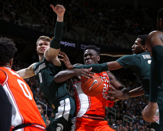 Illinois' Kofi Cockburn, center, and Michigan State's Kyle Ahrens, left, and Marcus Bingham Jr., right, compete for a rebound during the first half of an NCAA college basketball game Thursday, Jan. 2, 2020, in East Lansing, Mich. (AP Photo/Al Goldis)