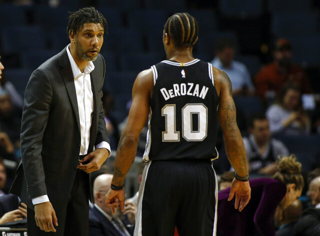 San Antonio Spurs acting head coach Tim Duncan, left, talks to San Antonio Spurs forward DeMar DeRozan in the first half of an NBA basketball game against the Charlotte Hornets in Charlotte, N.C., Tuesday, March 3, 2020. (AP Photo/Nell Redmond)