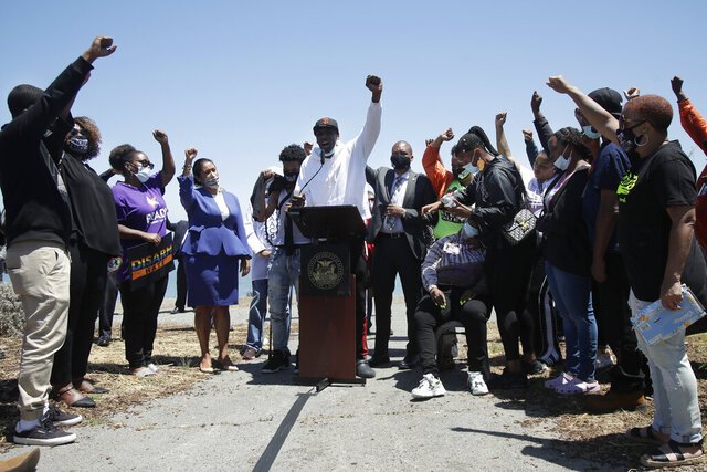 Jason Young, center, raises his fist while speaking at a news conference about the shooting death of his son, Jace Young, in San Francisco, Tuesday, July 7, 2020. Also pictured are Mayor London Breed, center left, and Jace Young's mother, LaKesha Young, seated center right. Breed called for an end to gun violence Tuesday at the gathering to mourn Jace Young, a 6-year-old African American boy who was shot while watching fireworks on the Fourth of July. Police are asking for witnesses for help in the Bayview-Hunters Point neighborhood. (AP Photo/Jeff Chiu)