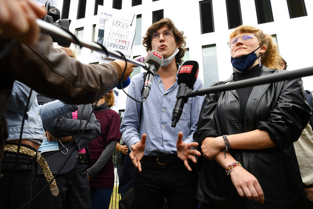 Pro-climate activists Paul Castelain, left, and.Claire Corbaz, right, talk to media after the guilty verdict of the trial of 12 pro-climate activists of the LAC collective (Lausanne Action Climat) that were prosecuted in appeal for organizing a tennis game in a Lausanne branch of Swiss bank Credit Suisse, in front of the court in Renens, Switzerland, Thursday, Sept. 24, 2020. (Laurent Gillieron/Keystone via AP)
