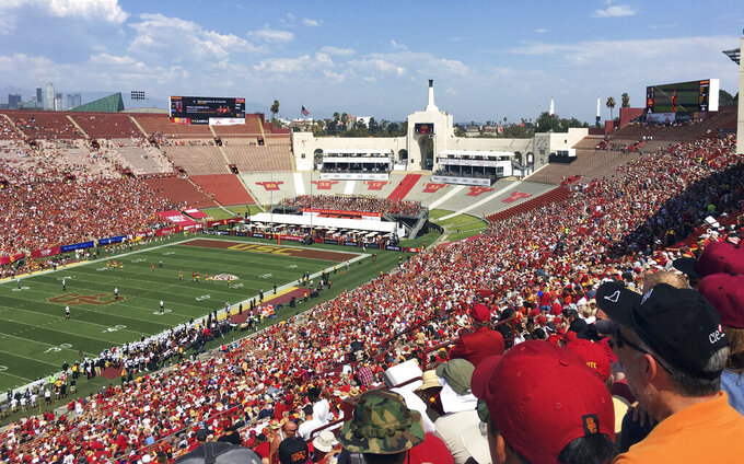 In this Sept. 2, 2017 photo, fans fill the Los Angeles Memorial Coliseum during a University of Southern California NCAA college football game in Los Angeles. United Airlines offered Friday, March 29, 2019, to withdraw from a $69 million deal to change Los Angeles Memorial Coliseum into United Airlines Memorial Coliseum following criticism that adding a corporate name is disrespectful to the facility's history of honoring troops who fought and died in World War I.  (AP Photo/John Antczak)