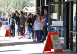 Voters wait in line to cast their ballots at a relocated polling station, Tuesday, Nov. 6, 2018 in Chandler, Ariz. The new polling station opened four hours late after the original location did not open due to the buildings' foreclosure overnight. (AP Photo/Rick Scuteri)