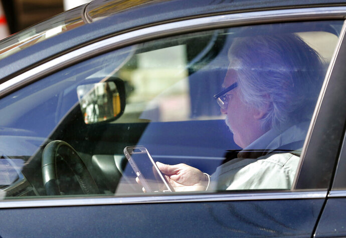 In this Thursday, May 16, 2019 photo, a driver uses his cell phone while driving in Portland, Maine. A bill to ban the use of handheld cellular devices while driving in the state goes into effect on Thursday, Sept. 19. (AP Photo/Robert F. Bukaty)