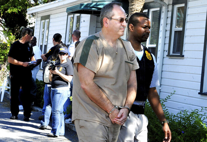 In this Feb. 2011 photo a DEA agent escorts Zvi Harry Perper to an awaiting police car after his Delray Pain Management clinic was raided by agents in Delray Beach, Fla.  Florida's 'pill mills' were a gateway to the nation's opioid crisis, feeding addiction and overdoses in Appalachia and other states. They exploded across Florida in the early 2000s and operated for years with little oversight. The release this week of July 19, 2019,  of a trove of federal data showing the distribution of opioids across the U.S. put the spotlight again on Florida's notorious 'pill mills,' which provided the seeds of an epidemic that continues to cost tens of thousands of lives each year.  (Carline Jean/South Florida Sun-Sentinel via AP)