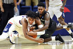 Connecticut's Josh Carlton, left, and Tulane's Jordan Walker, right, battle for a loose ball in the first half of an NCAA college basketball game Wednesday, Jan. 8, 2020, in Storrs, Conn. (AP Photo/Stephen Dunn)
