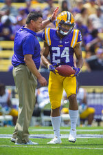 FILE - In this April 6,2019, file photo, LSU coach Ed Orgeron, left, gives freshman cornerback Derek Stingley Jr. (24) a pat on the head after talking with him briefly after Stingley fielded a punt during the NCAA college football team's spring scrimmage n Baton Rouge, La. Stingley was the nation's No. 1 prospect in his class according to Rivals and was rated third according to the 247Sports Composite. Travis Spradling/The Advocate via AP, File)