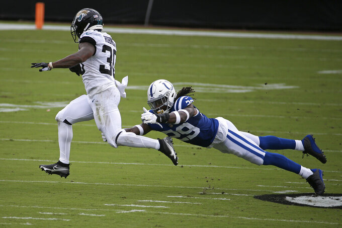 Jacksonville Jaguars running back James Robinson (30) slips past Indianapolis Colts free safety Malik Hooker for a gain during the first half of an NFL football game, Sunday, Sept. 13, 2020, in Jacksonville, Fla. (AP Photo/Stephen B. Morton)