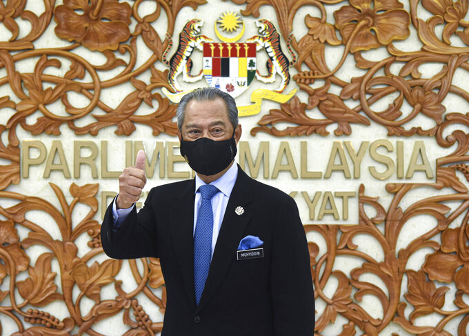In this photo released by Malaysia's Information Ministry, Prime Minister Muhyiddin Yassin poses for a picture at the parliament, in Kuala Lumpurf, Malaysia Thursday, Nov. 26, 2020. Malaysia's Parliament Thursday approved the government's proposed 2021 budget, throwing a political lifeline to embattled Prime Minister Muhyiddin Yassin amid strong resistance to his nine-month-old leadership. (Zarith Zulkifli/Malaysia's Department of Information via AP)