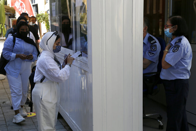 A woman wearing protective face mask, shows her COVID-19 test to a police officer at Ledra crossing point in divided capital Nicosia, Cyprus, Friday, June 4, 2021. Ethnically split Cyprus took a key step toward a return to its normal rhythms of life amid the pandemic on Friday when nine crossing points along a United Nations-controlled buffer zone were reopened, enabling ordinary Cypriots to cross the divide. (AP Photo/Petros Karadjias)