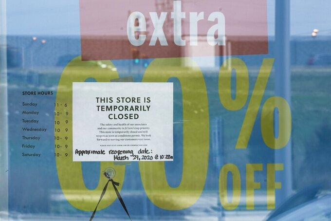 A closed sign hangs on the door outside J. Crew on Wednesday April 15, 2020, in Wauwatosa, Wis. (AP Photo/Morry Gash)