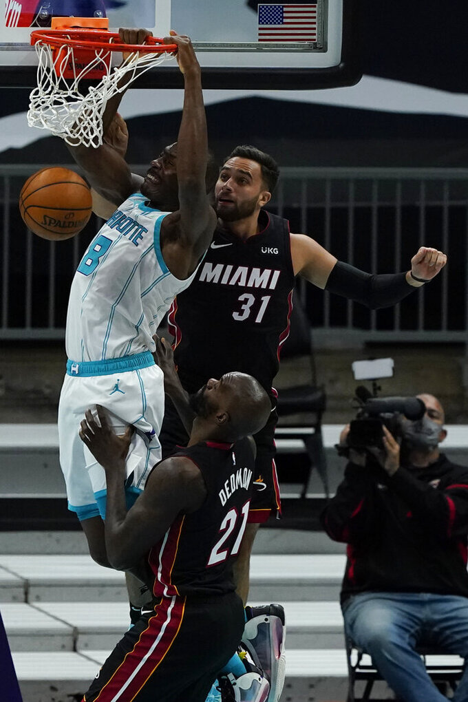 Charlotte Hornets center Bismack Biyombo dunks past Miami Heat guard Max Strus (31) and center Dewayne Dedmon during the first half of an NBA basketball game on Sunday, May 2, 2021, in Charlotte, N.C. (AP Photo/Chris Carlson)