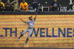 Los Angeles Dodgers right fielder Chris Taylor can't make the catch on a two-run home run hit by San Diego Padres' Fernando Tatis Jr. during the fifteenth inning of a baseball game Thursday, Aug. 26, 2021, in San Diego. (AP Photo/Gregory Bull)