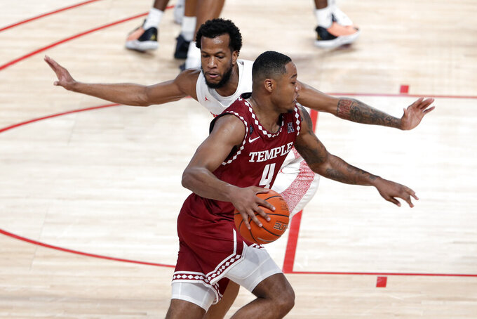 Temple forward J.P. Moorman II (4) drives around Houston forward Justin Gorham, back, during the second half of an NCAA college basketball game Tuesday, Dec. 22, 2020, in Houston. (AP Photo/Michael Wyke)