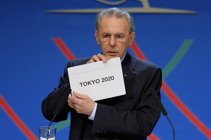 FILE - In this Saturday, Sept. 7, 2013 file photo, International Olympic Committee (IOC) President Jacques Rogge shows the name of the city of Tokyo elected to host the 2020 Summer Olympics in Buenos Aires, Argentina. The International Olympic Committee on Sunday, Aug, 29, 2021 says Jacques Rogge who led the organization as president for 12 years, has died. He was 79. (Fabrice Coffrini/Pool photo via AP, file)