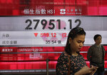 People walk past a bank electronic board showing the Hong Kong share index at Hong Kong Stock Exchange Tuesday, May 14, 2019. Shares opened moderately lower in Asia on Tuesday after a dismal day on Wall Street as investors fled uncertainty over the China-U.S. trade standoff. (AP Photo/Vincent Yu)