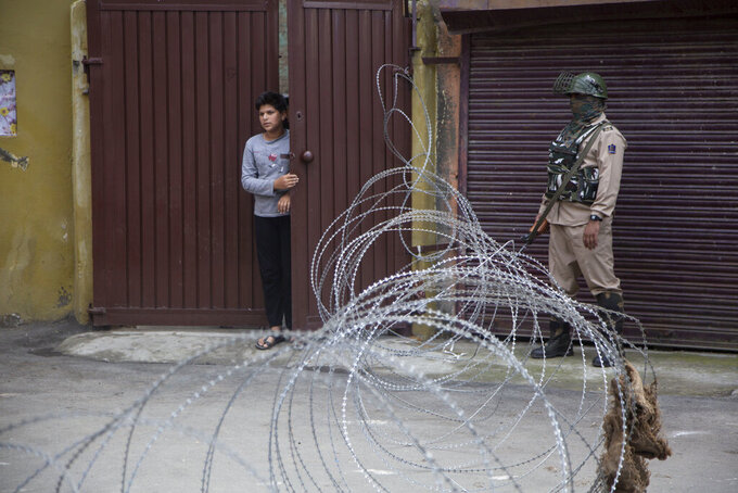 A young Kashmiri boy looks out from the gate of his house as an Indian paramilitary soldier stands guard at a check point during a restrictions in Srinagar, Indian controlled Kashmir, Saturday, Aug. 29, 2020. Authorities had imposed restrictions in parts of Srinagar, the region's main city, to prevent gatherings marking Muharram from developing into anti-India protests. (AP Photo/Mukhtar Khan)