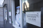 Medical workers in a booth wait for people to come for tests at a coronavirus testing site in Seoul, South Korea, Tuesday, Jan. 19, 2021. (AP Photo/Ahn Young-joon)