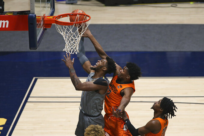 West Virginia forward Derek Culver (1) shoots while defended by Oklahoma State forward Matthew-Alexander Moncrieffe (12) during the first half of an NCAA college basketball game Saturday, March 6, 2021, in Morgantown, W.Va. (AP Photo/Kathleen Batten)