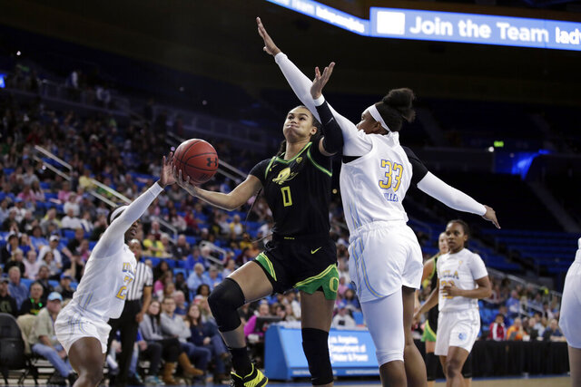 Oregon's Satou Sabally (0) shoots next to UCLA forward Lauryn Miller (33) during the first half of an NCAA college basketball game Friday, Feb. 14, 2020, in Los Angeles. (AP Photo/Marcio Jose Sanchez)