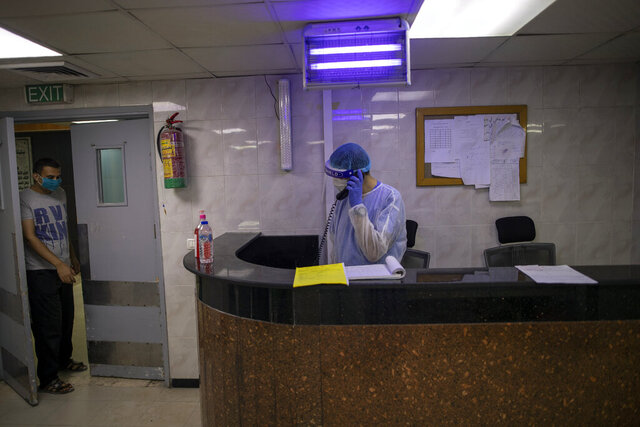 Palestinian doctors wear protective clothes as they work at the emergency room of the al-Quds Hospital in Gaza City, Monday, Sept. 7, 2020. Dozens of front-line health care workers have been infected, dealing a new blow to overburdened hospitals. (AP Photo/Khalil Hamra)
