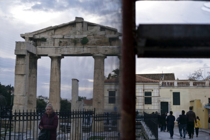 People are seen through the netting of a scaffolding as they walk in front of the Gate of the ancient Roman agora in Plaka district of Athens on Wednesday, Jan. 23, 2019. (AP Photo/Petros Giannakouris)