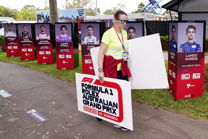 A woman takes away signs after the cancellation of the Australian Formula One Grand Prix in Melbourne, Friday, March 13, 2020. The first F1 Grand Prix of the season was canceled two hours before the first official practice was set to start Friday after organizers relented to pressure to call it off amid the spreading coronavirus. (Michael Dodge/AAP Image via AP)