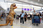 Tourists pass by a protester dressed as a dinosaur during a demonstration at the airport in Hong Kong Friday, Aug. 9, 2019. Pro-democracy activists rallied at Hong Kong's airport Friday even as the city sought to reassure visitors of their welcome despite the increasing levels of violence surrounding the 2-month-old protest movement. (AP Photo/Vincent Thian)