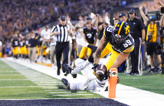 Iowa wide receiver Nico Ragaini (89) dives to score a touchdown in front of Penn State safety Ji'Ayir Brown (16) during the second half of an NCAA college football game, Saturday, Oct. 9, 2021, in Iowa City, Iowa. Iowa won 23-20. (AP Photo/Matthew Putney)
